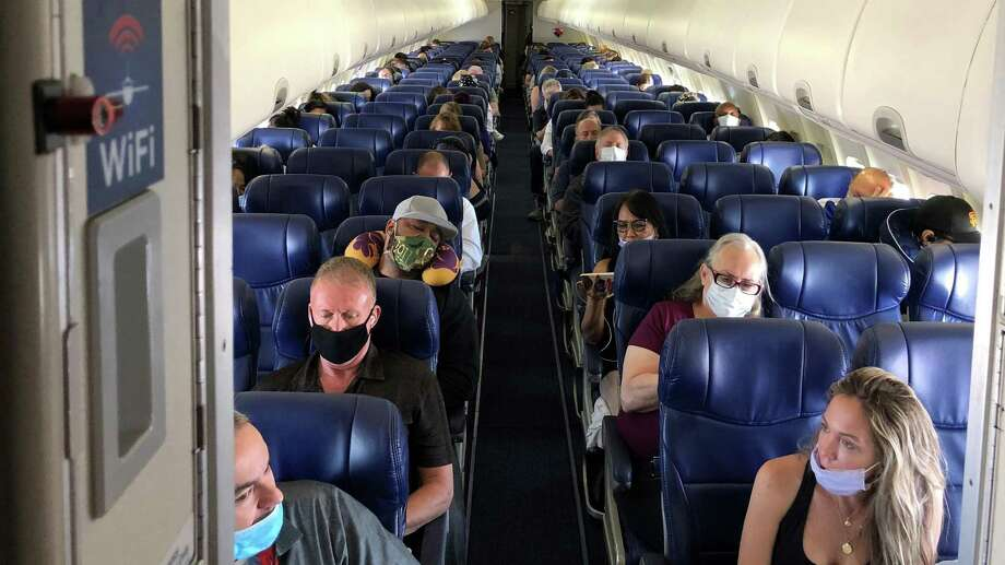 Masked passengers fill a Southwest Airlines flight from Burbank, Calif., to Las Vegas on June 3. Now carriers are finally getting tough, banning passengers who refuse to put on masks — even though the airlines desperately need the revenue to stay in business. Photo: Christopher Reynolds /Los Angeles Times / Los Angeles Times
