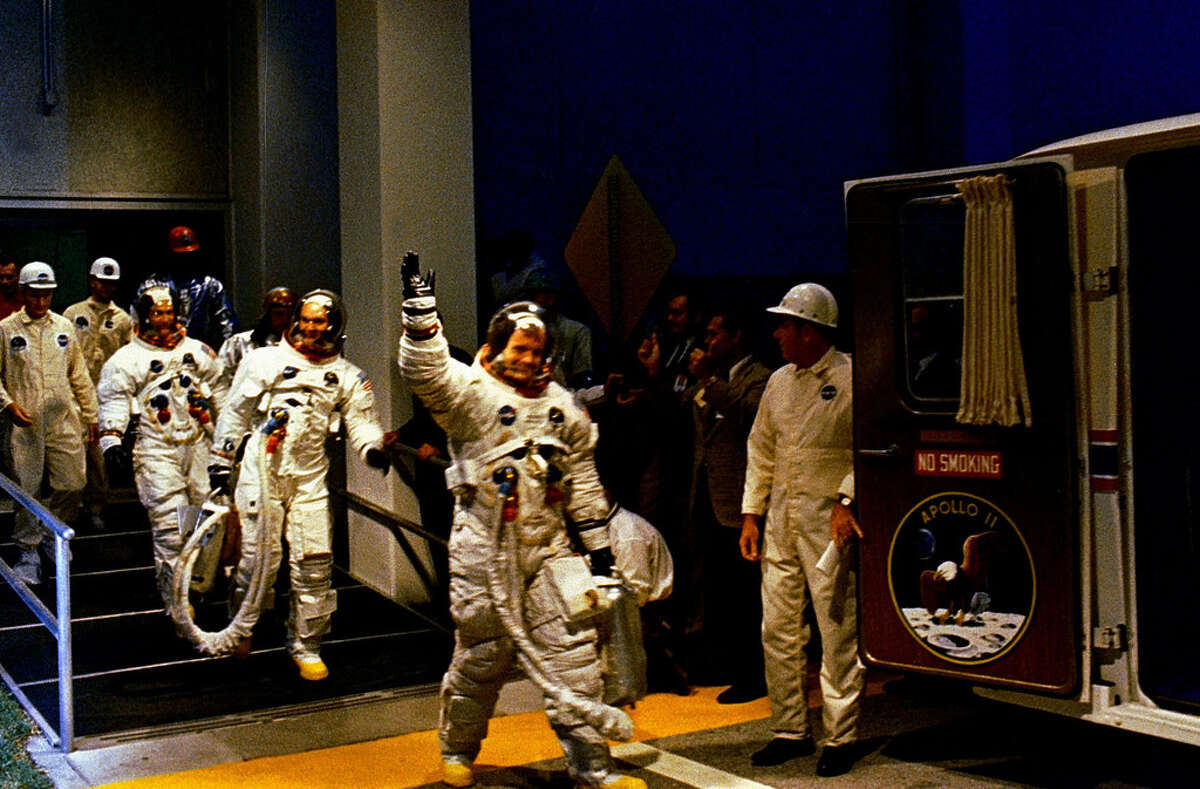 The Apollo 11 crew leaves Kennedy Space Center's Manned Spacecraft Operations Building during the pre-launch countdown. Mission commander Neil Armstrong, command module pilot Michael Collins, and lunar module pilot Buzz Aldrin prepare to ride the special transport van to Launch Complex 39A where their spacecraft awaited them. Liftoff occurred at 9:32 a.m. EDT, July 16, 1969. (NASA photo archive)