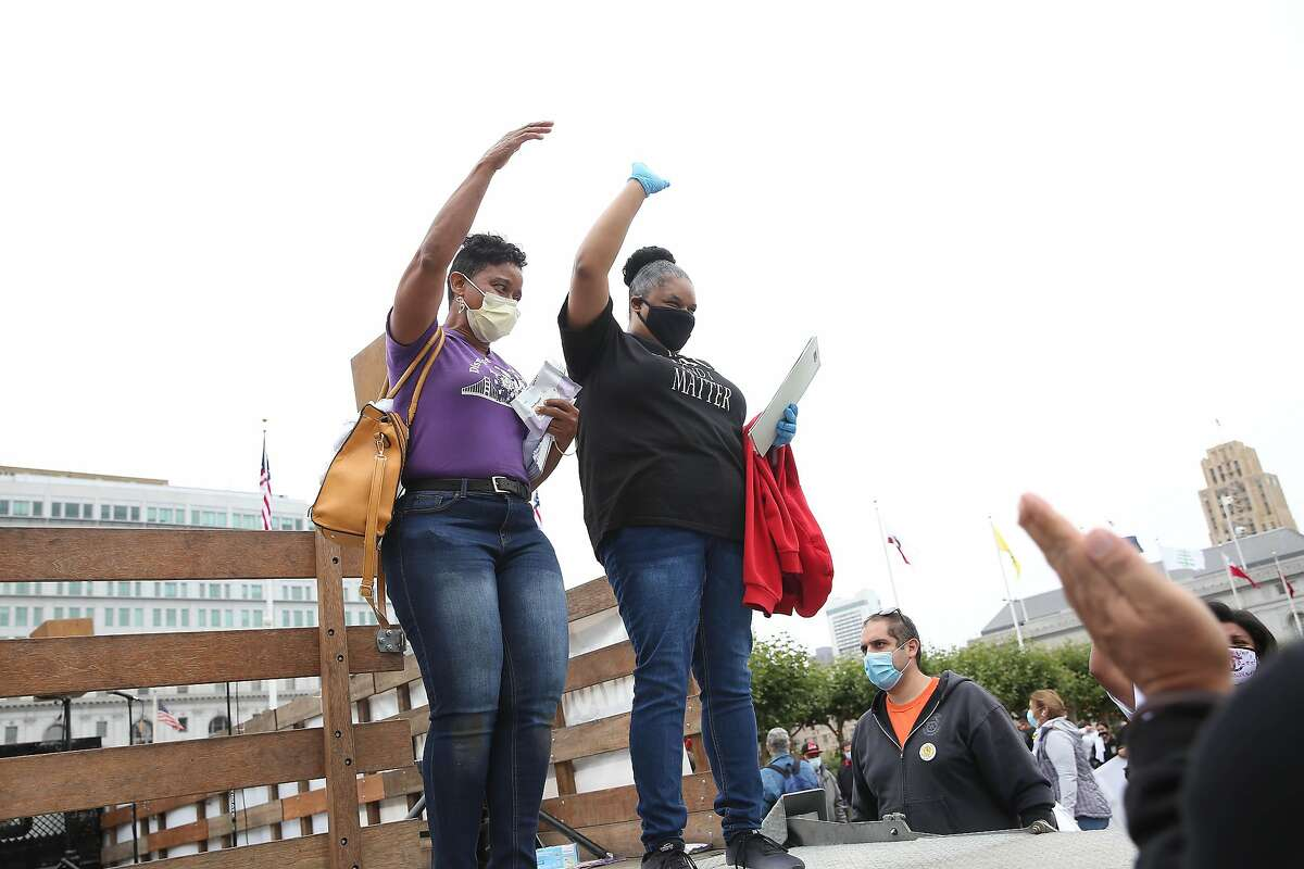 Theresa Rutherford (l to r), vice president of SEIU 1021 and Nicole Christian, SEIU member, hold their fists in the air as people applaud after thjey spoke at a Strike for Black Lives protest at City Hall on Monday, July 20, 2020 in San Francisco, Calif.