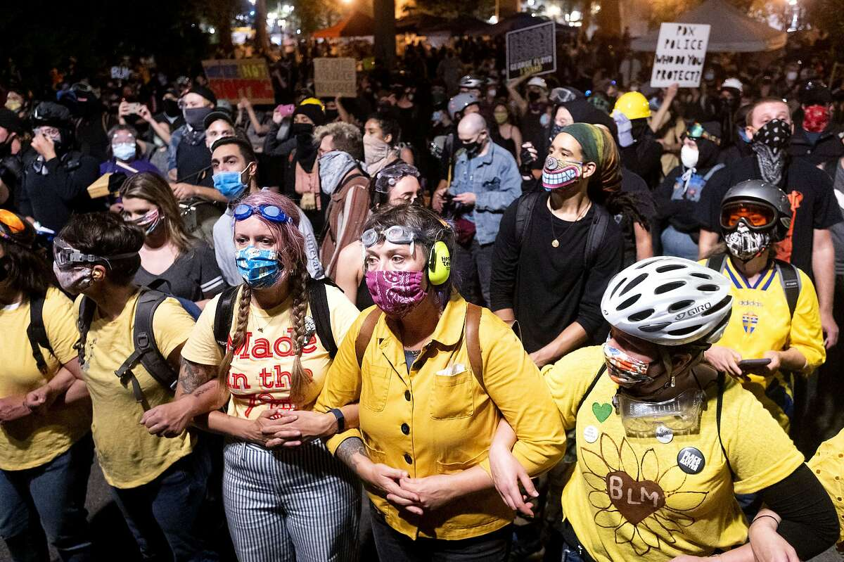 Black Lives Matter protesters gather outside the Mark O. Hatfield United States Courthouse on Sunday, July 19, 2020, in Portland, Ore. Officers used teargas and projectiles to move the crowd after some protesters tore down a fence fronting the courthouse. (AP Photo/Noah Berger)