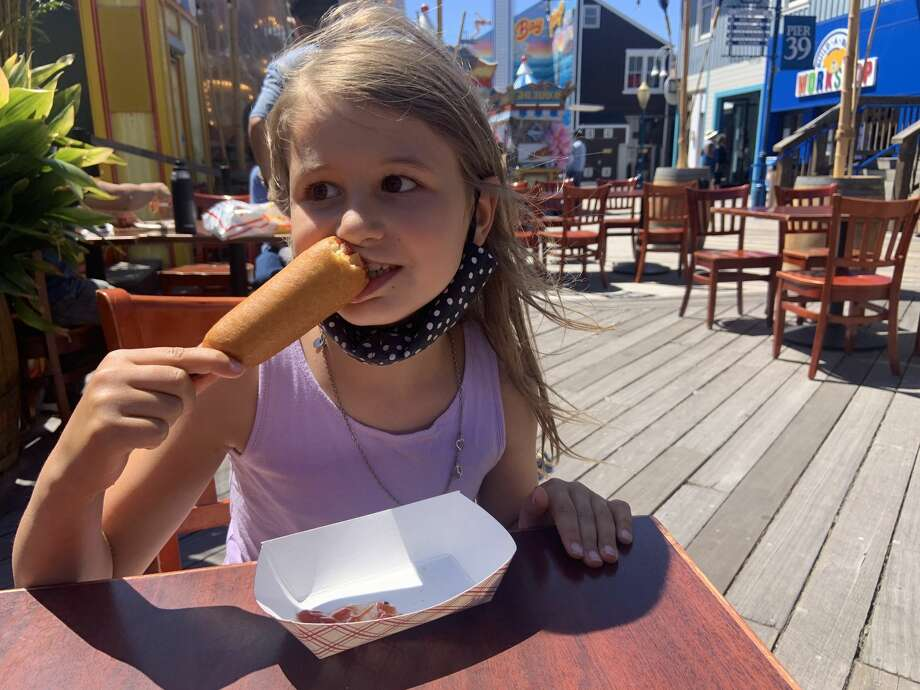 A girl eats her first corn dog at Pier 39 in San Francisco, Calif., on July 12, 2020. Photo: Amy Graff