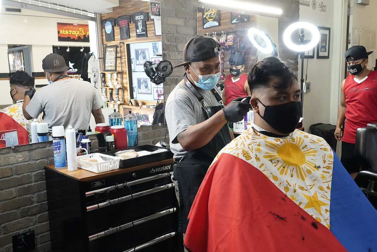 Streetset University Barbershop and Boutique, co-owner Case Dofredo give a haircut to Bart Bumanglag at their reopening after closing for four months during for the coronavirus shutdown on Monday, July 13, 2020 in San Jose, Calif. Co-owner C.J. Pangayan is at right.