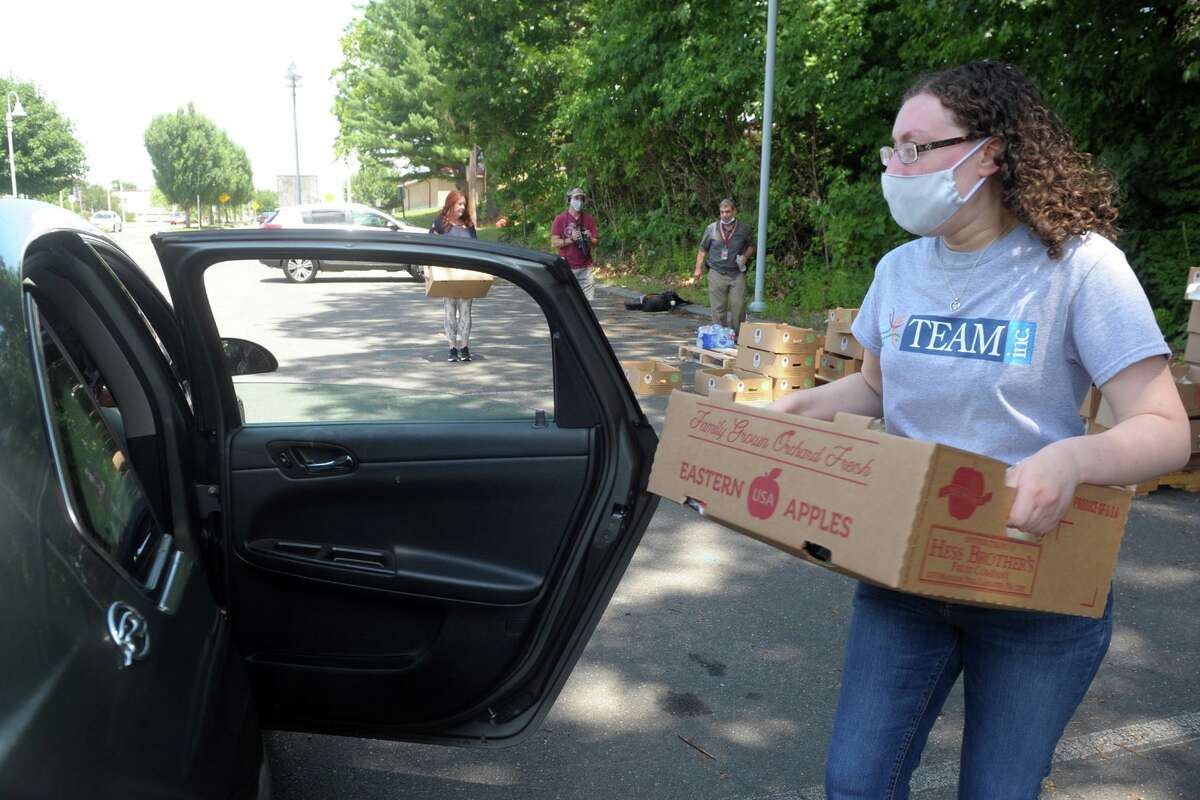 Josylnn Hernandez, of Seymour, loads a box of fresh produce into a waiting car during the TEAM Inc. drive-through food donation at Derby High School, in Derby, Conn. July 20, 2020. Boxes containing nearly 24 pounds of food will be distributed at Ansonia's Nolan Field on Oct. 6 from noon to 6:30 p.m.