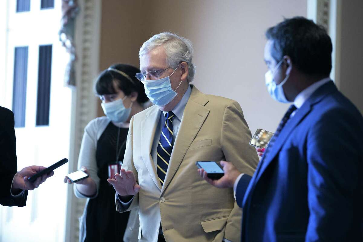 Senate Majority Leader Mitch McConnell, a Republican from Kentucky, wears a protective mask while speaking to members of the media as he walks to his office at the U.S. Capitol in Washington D.C., U.S. on Monday, July 20, 2020. McConnell and President Donald Trump met today to hammer out the Republican plan for the next virus relief bill amid firm opposition from Democrats who say the GOP is tilting aid toward businesses instead of people struggling with the expanding pandemic. Photographer: Stefani Reynolds/Bloomberg