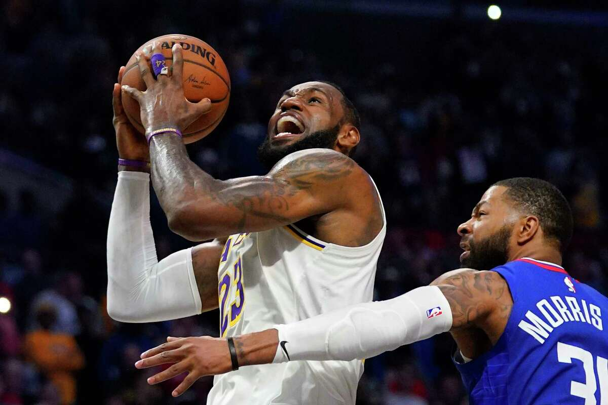 FILE - In this March 8, 2020, file photo, Los Angeles Lakers forward LeBron James, left, shoots as Los Angeles Clippers forward Marcus Morris Sr. defends during the second half of an NBA basketball game in Los Angeles. The NBA is a few weeks from playoff mode, and James has himself and the Lakers squarely in the mix to compete for championship. It is a rare bit of normalcy for a player who appeared in eight consecutive NBA Finals from 2011 through and including 2018, and for a franchise that has won 16 championships. (AP Photo/Mark J. Terrill, File)