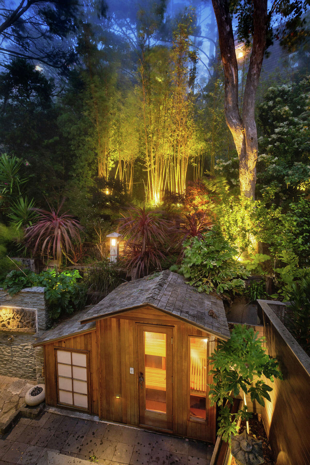 Not your everyday townhouse backyard. Here we see the sauna and layered foliage lit up at dusk.