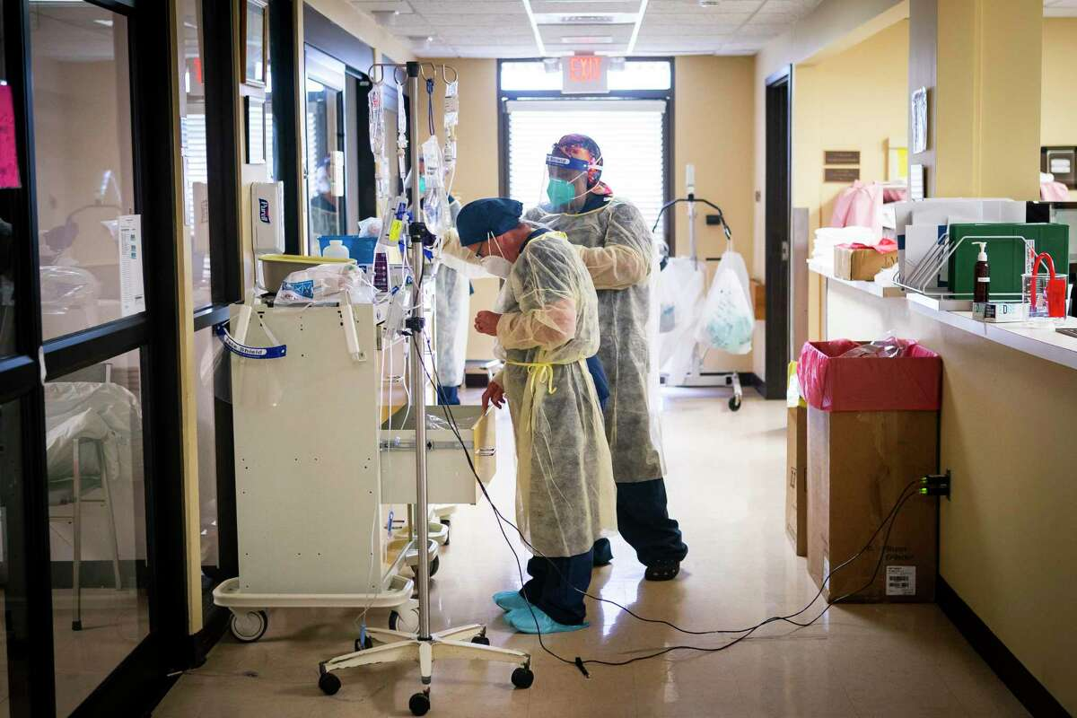 Nurses put on extra protective equipment while working in the hospital's four bed ICU, Monday, July 20, 2020, at El Campo Memorial Hospital in El Campo, TX. The small, rural hospital currently has three out of their four ICU beds filled with COVID-19 positive patients.