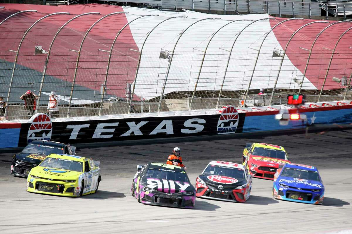 A NASCAR official checks drivers as the race was red flagged for over 11 minutes due to an 11-car incident during a NASCAR Cup Series auto race at Texas Motor Speedway in Fort Worth, Texas, Sunday, July 19, 2020. (AP Photo/Ray Carlin)