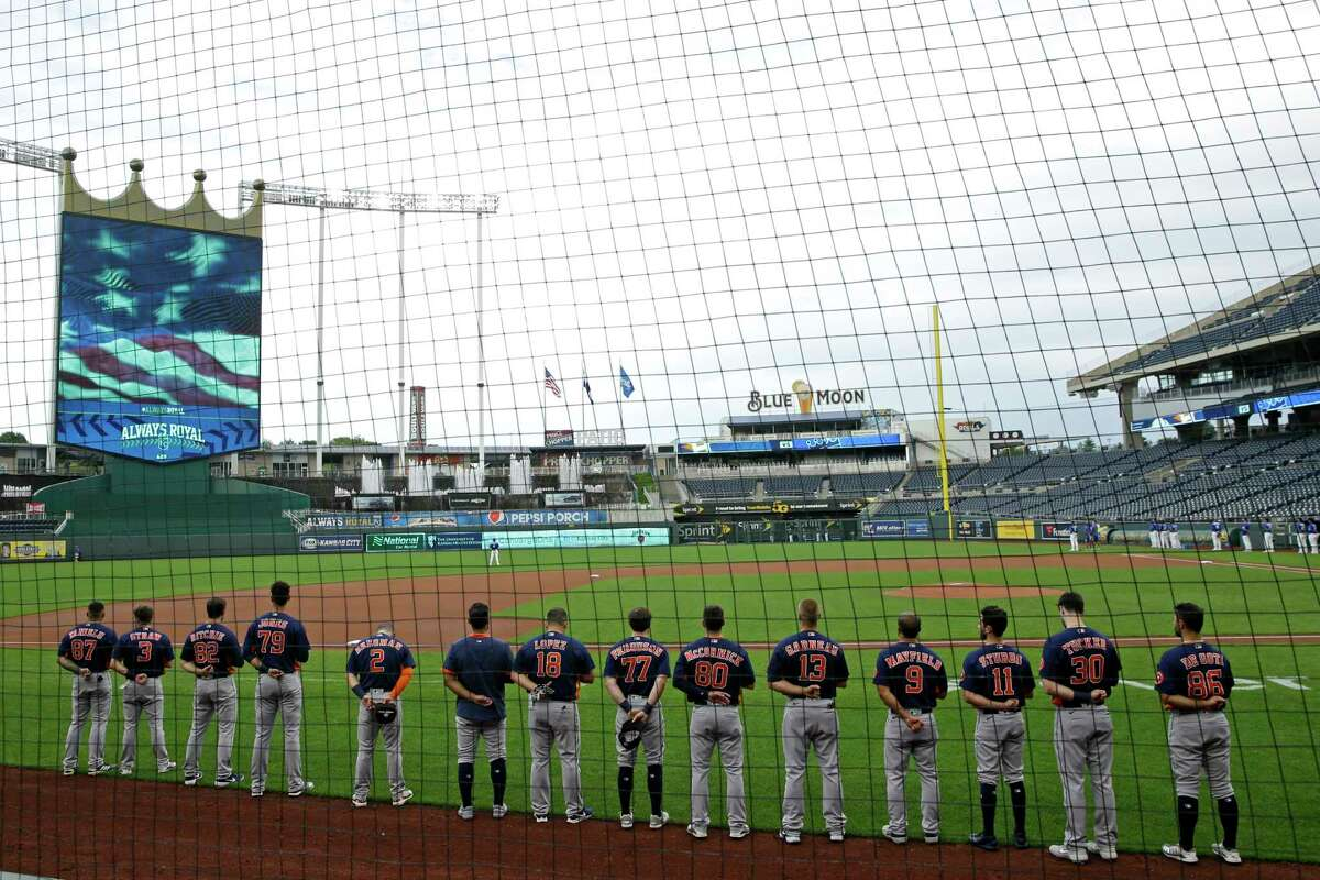 Houston Astros players stand for the national anthem before an exhibition baseball game against the Kansas City Royals in Kansas City, Mo., Monday, July 20, 2020. (AP Photo/Charlie Riedel)