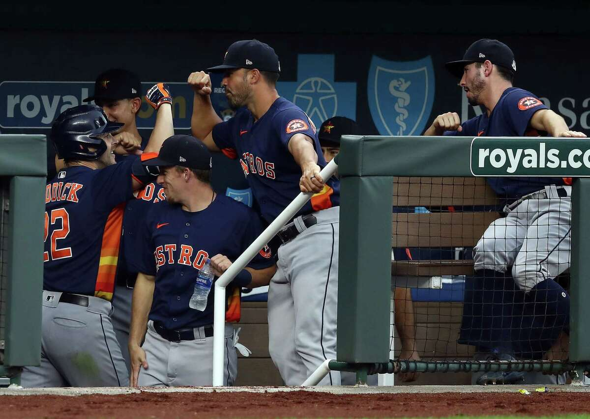 KANSAS CITY, MISSOURI - JULY 20: Josh Reddick #22 of the Houston Astros is congratulated by teammates in the dugout after hitting a 2-run home run during the 4th inning of an exhibition game against the Kansas City Royals at Kauffman Stadium on July 20, 2020 in Kansas City, Missouri.