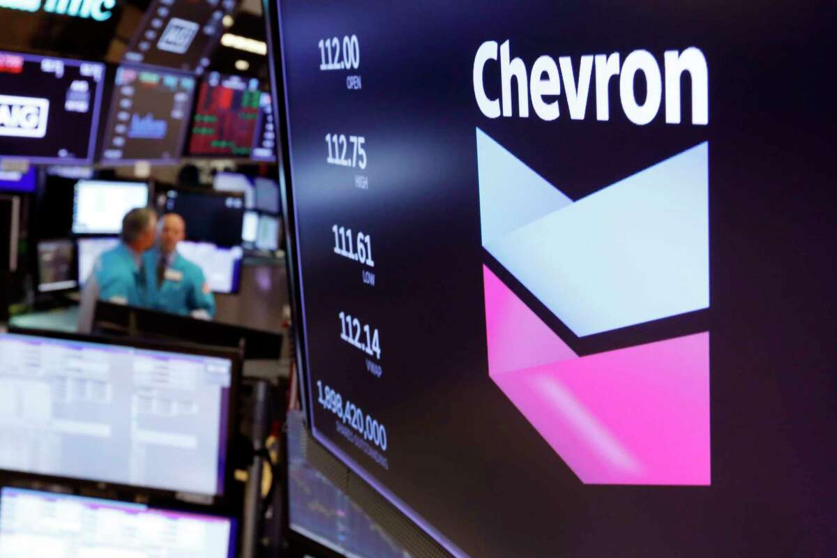 FILE - This Oct. 8, 2019, file photo the logo for Chevron appears above a trading post on the floor of the New York Stock Exchange. Chevron Corp. says it will acquire Noble Energy in an all-stock deal valued at $5 billion. The San Ramon, California-based Chevron has been shopping for an acquisition for months as oil prices have tanked due to the coronavirus outbreak. (AP Photo/Richard Drew, File)