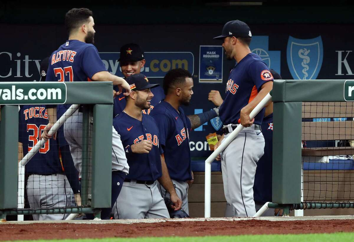 KANSAS CITY, MISSOURI - JULY 20: Martin Maldonado #15 of the Houston Astros is congratulated by teammates in the dugout after hitting a 2-run home run during the 4th inning of an exhibition game against the Kansas City Royals at Kauffman Stadium on July 20, 2020 in Kansas City, Missouri.