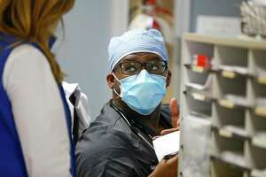 Dr. Gabriel Agbanyim speaks with case manager Jeanne Ocanas about a patient that may need to be transferred out of the hospital, Monday, July 20, 2020, at El Campo Memorial Hospital in El Campo, TX. The small, rural hospital has created an isolated hallway for COVID patients as well as accepting COVID patients in their four ICU beds.