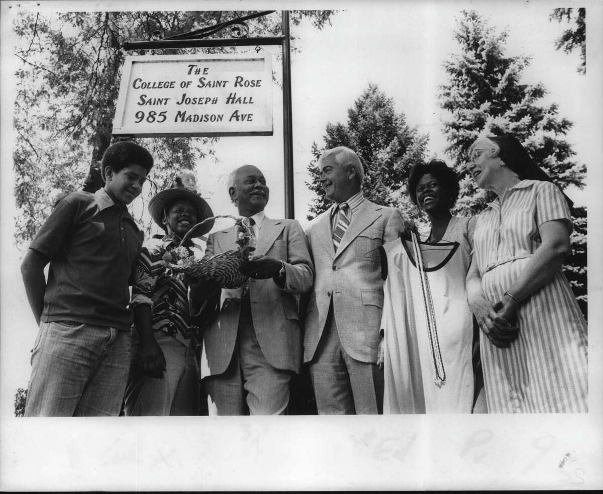 Dan Stevens, Elaine Smith, Dr James Smouth, Chairman of the College Board of Trustees; Dr Thomas Manion, St Rose College President; Cynthia Brandon and Sister Noel Marie Cronin, Growth and Progress Director, stand in front of sign for The College of Saint Rose, Saint Joseph Hall, 985 Madison Avenue, Albany, New York. August 23, 1975 (H. Brian Triller/Times Union Archive)