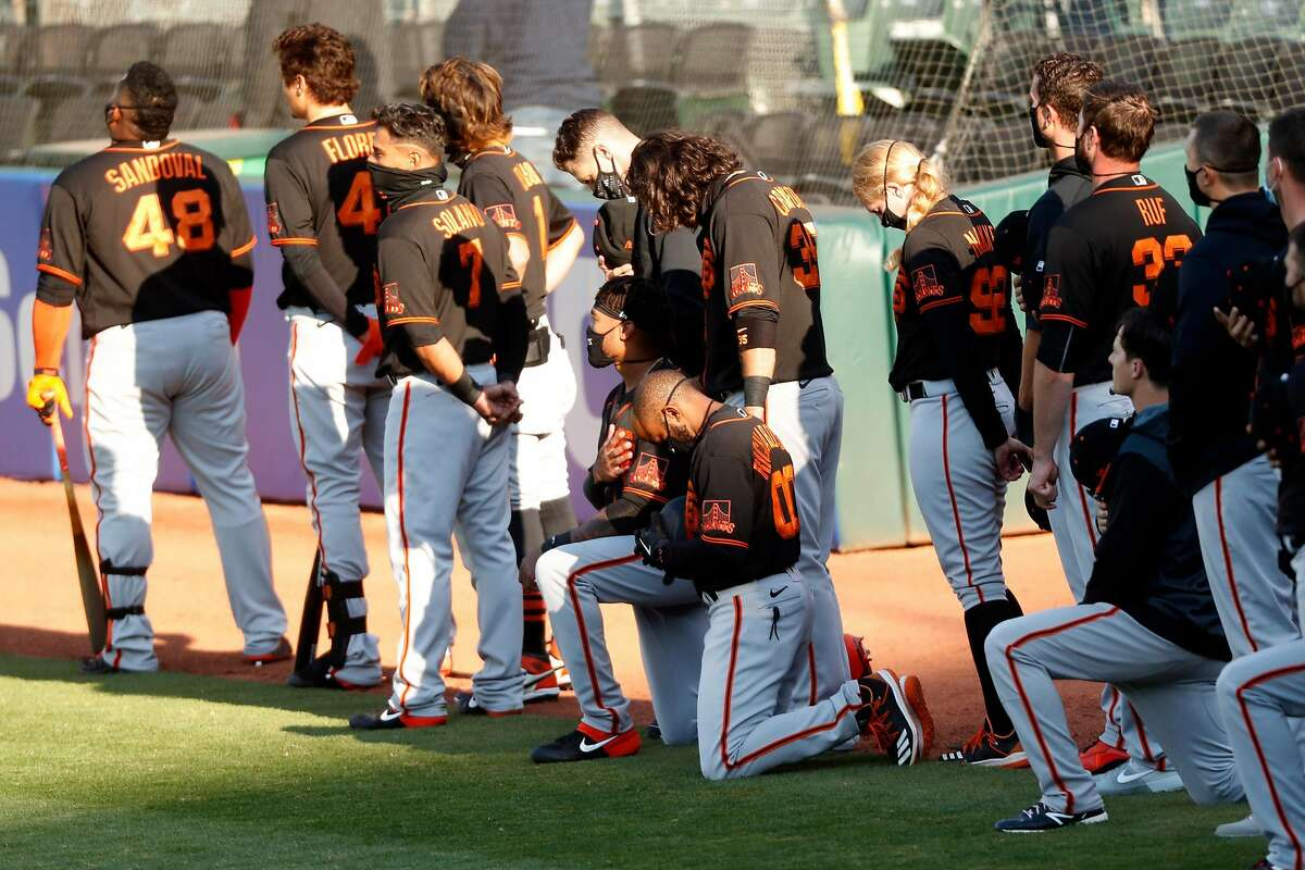 San Francisco Giants' coach Antoan Richardson (00) and Jaylin Davis kneel during National Anthem before playing Oakland Athletics in exhibition game at Oakland Coliseum in Oakland, Calif., on Monday, July 20, 2020.