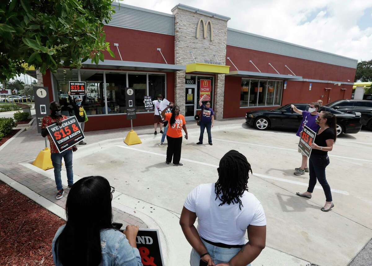 Demonstrators protest outside a McDonald's restaurant, Monday, July 20, 2020, in Fort Lauderdale, Fla. Organizers of a national workers strike say tens of thousands are set to walk off the job Monday morning in more than two dozen U.S. cities, to protest systemic racism and economic inequality that has only worsened during the coronavirus pandemic. (AP Photo/Wilfredo Lee)