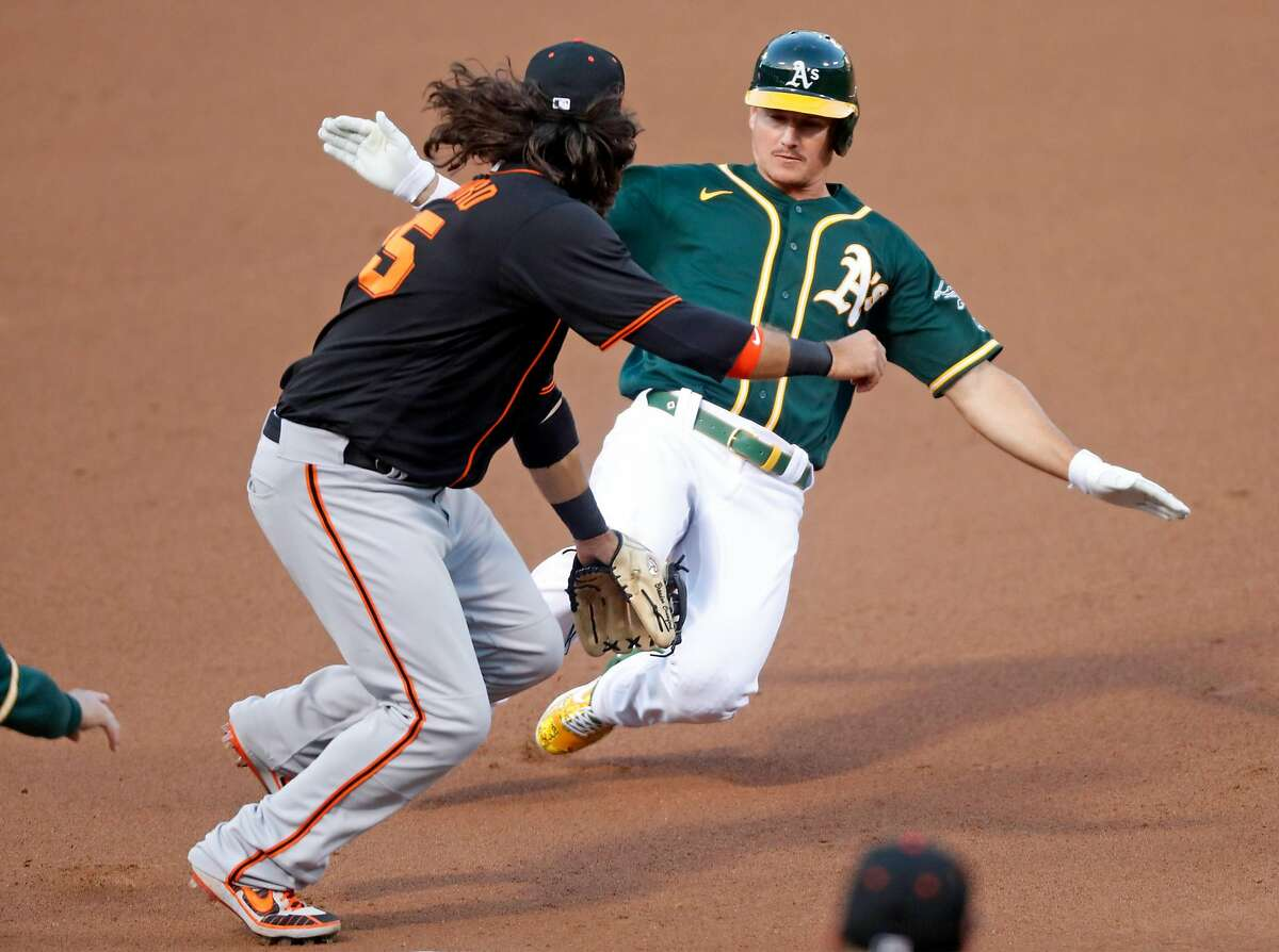 Oakland Athletics' Matt Chapman slides into third base on Matt Olson's 4th inning double as San Francisco Giants' Brandon Crawford awaits the throw during exhibition game at Oakland Coliseum in Oakland, Calif., on Monday, July 20, 2020.
