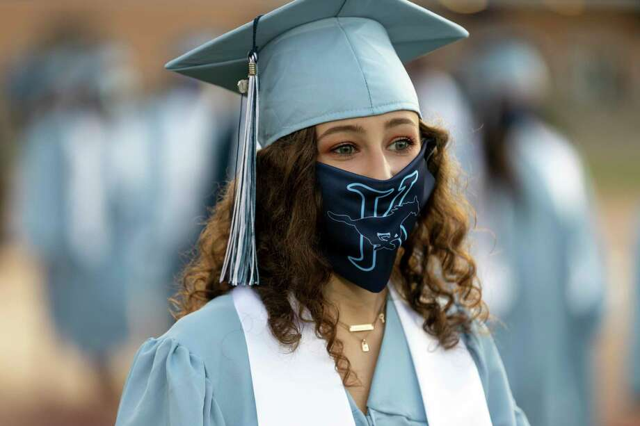 A graduate wears a custom face mask that was given to each graduate during a Kingwood High School graduation ceremony held at Turner Stadium in Humble, Monday, July 20, 2020. An estimated 520 students walked across the stage to celebrate commemorate their graduation. Photo: Gustavo Huerta, Houston Chronicle / Staff Photographer / Houston Chronicle © 2020