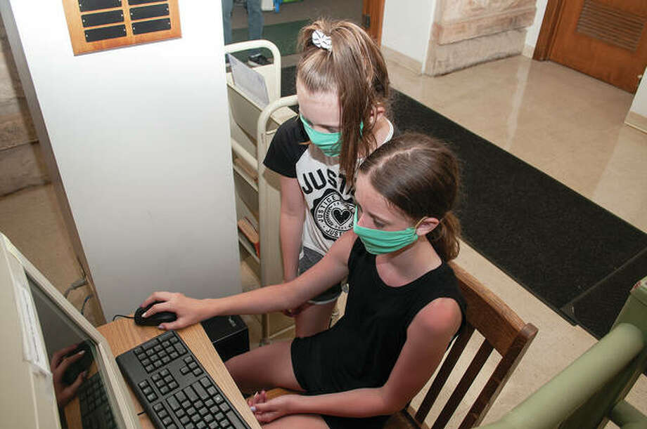 Thea Laumakis (left), 8, and her sister, Lexi, 10, work together Monday to order a book at Jacksonville Public Library. The library is open but requires masks and social distancing. Library hours for the general public are from 10 a.m. to 6 p.m. weekdays, from 10 a.m. to 5 p.m. Saturday and from noon to 4 p.m. Sunday. The library is reserved from 9 to 10 a.m. Monday through Saturday for senior patrons. Photo: Darren Iozia | Journal-Courier