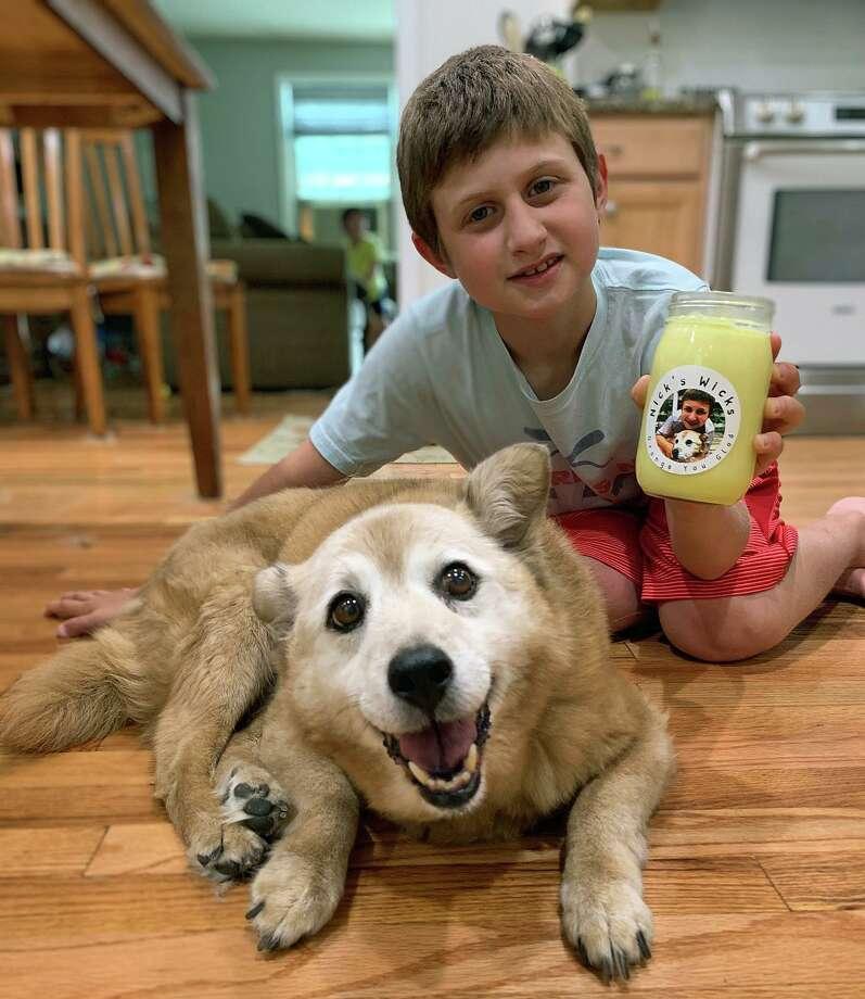 Nick Vigliotti détient un de ses faits à la main des bougies de soja, son de 13 ans, chien de sauvetage se trouve à proximité. Il fera un don de 30 pour cent de son mois de juillet le bénéfice de Murphy de la Patte de Sauvetage. Photo: Sarah Kyrcz / Pour Hearst Connecticut Médias