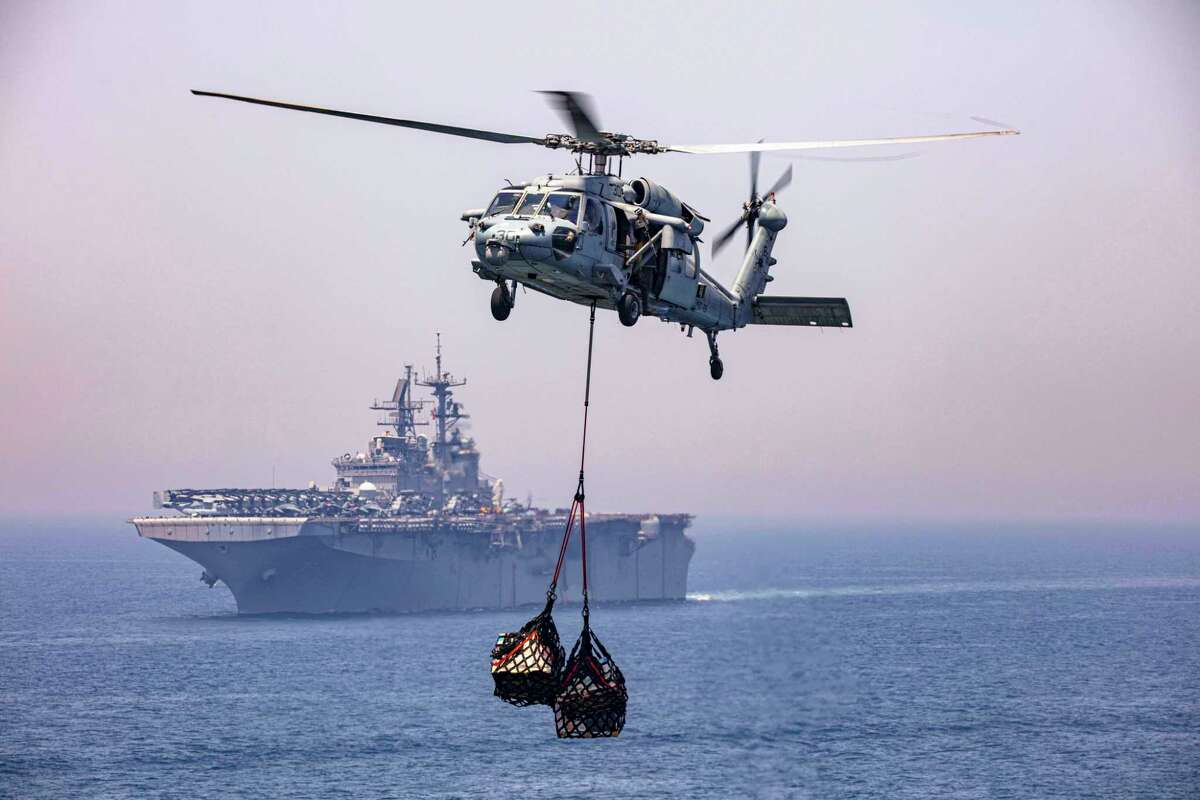 """An MH-60S Seahawk helicopter during a supply lift on April 25, 2020, while attached to the """"Dragon Whales"""" of Helicopter Sea Combat Squadron (HSC) 28 in the vicinity of the amphibious assault ship USS Bataan (LHD 5). (U.S. Navy photo by Mass Communication Specialist 2nd Class Lyle Wilkie/Released)"""