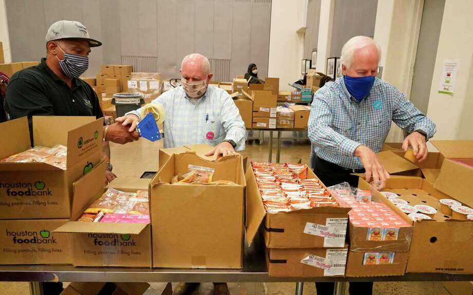 Herschel Minifee, volunteer services rep., left, hand tape to U.S. Secretary of Agriculture Sonny Perdue, center, as he and U.S. Senator John Cornyn, right, pack boxes at the Houston Food Bank during a tour led by president Brian Greene Thursday, July 16, 2020, in Houston. Greene spoke about the Food Bank's response to increased demand in southeast Texas during the pandemic. The tour was also in advance of the Senate's debate of a fifth coronavirus relief bill this month. The Houston Food Bank, the nation's largest food bank, serves 18 counties in southeast Texas, and in June alone delivered more than 27 million pounds of food. Photo: Melissa Phillip, Houston Chronicle / Staff Photographer / © 2020 Houston Chronicle