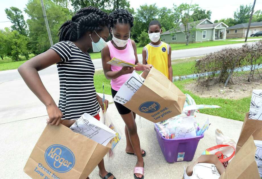 Siblings (from left) Mylah, Zibrianna and Damon Thomas select activity bags as they stop with their mother Catherine Thomas at the home of neighbor Karen Douresseau on Pine Street in Beaumont Tuesday. Douresseau, a longtime librarian with Beaumont schools who retired last fall from Martin Elementary and heads up children's activities at Mt. Goliad Church, was looking for a way to help children in the community navigate the life changes brought on by coronavirus and decided to assemble bags filled with games, toys, activities and reading materials, which she set outside for children in the community to take.  Photo taken Tuesday, July 14, 2020 Kim Brent/The Enterprise Photo: Kim Brent / The Enterprise / BEN