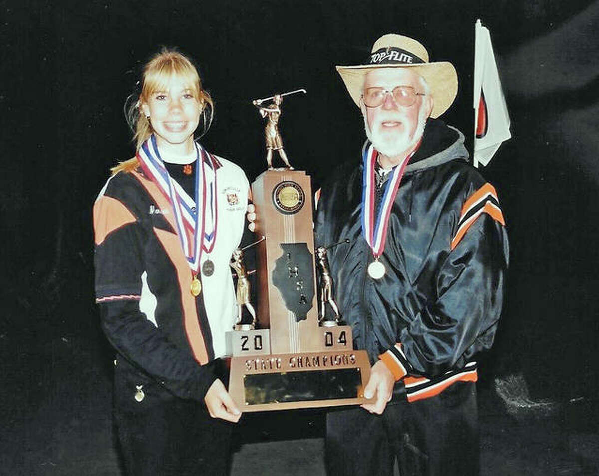 Edwardsville golfer Marissa Cook and EHS coach Gary Bair pose with the championship trophy after winning the 2004 state tournament at Stone Creek Golf Course. Cook, who was a freshman, placed second as an individual.