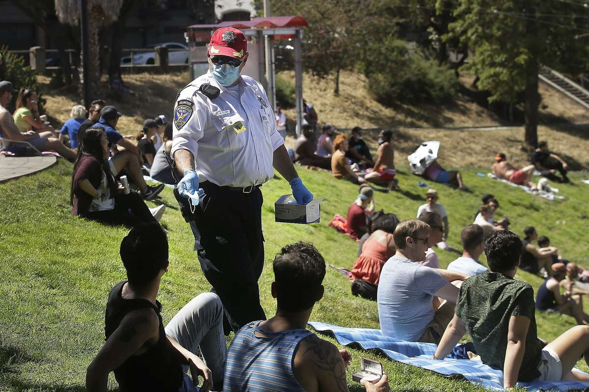 FILE - San Francisco Police Auxiliary Law Enforcement Response Team (ALERT) volunteer David Flynn offers face masks to help prevent the spread of the coronavirus at Dolores Park in San Francisco, Sunday, May 24, 2020. California is creating roving
