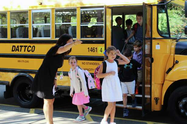 "Ashley Furnari, the assistant principal at West School in New Canaan, Connecticut, directs students off the bus at the school, on the first day of school, at the beginning of a recent school year. Parents will have a multiple choice question to answer this fall when the 2020-21 school year. The questions are going to be: Should their children continue remote learning or attend school, and for what period of time? The options are all in keeping with the state's guidelines for the coronavirus amid the pandemic from the virus, but the new ""fluidity"" adds a range of new challenges for educators."