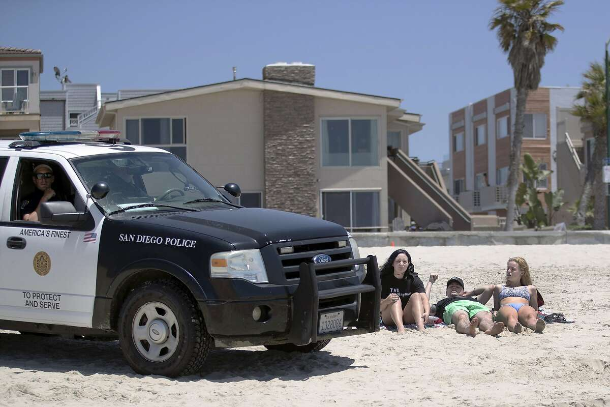 FILE - In this May 22, 2020, file photo, San Diego police officers ask three people to get up from the beach, which was closed to sitting or lying down, in San Diego. California is creating roving