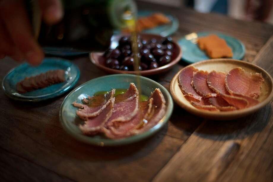 Seth Cripe drizzles olive oil over mojama, a salt-cured dried blackfin tuna loin. Photo: Erik Castro / Special To The Chronicle