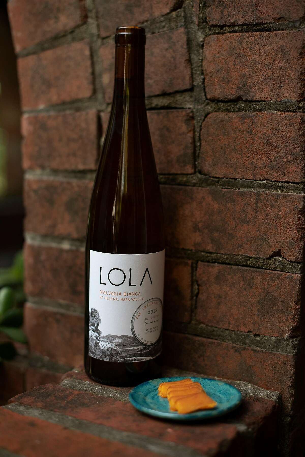A bottle of Lola Malvasia Bianca from St. Helena with a plate of Cortez bottarga at Lola Wines tasting room located in an 1890s building in Calistoga, California, on Thursday, March 19, 2020.
