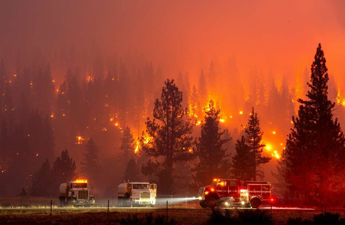 In this long exposure photograph, firefighters mop up hot spots from the Hog fire along highway 36 about 5 miles from Susanville, California on July 20, 2020. - The fire exploded to more than 6,000 acres and created its own weather, generating lightning, thunder, rain and fire whirls out of a huge pyrocumulonimbus ash plume towering above. The Lassen County Sheriff's office issued a mandatory evacuation order for the area.