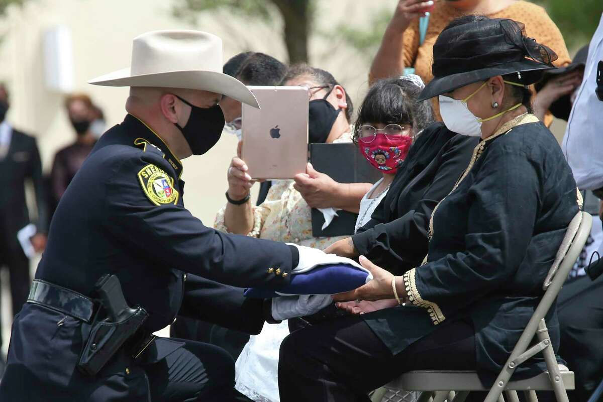 Bexar County Sheriff Javier Salazar offers the Texas flag to Pauline De La Fuente, widow of Deputy Timothy De La Fuente, during committal services at Community Bible Church, Tuesday, July 21, 2020.