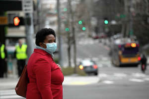 SEATTLE, WASHINGTON - MARCH 10: A masked pedestrian pauses near the Amazon headquarters on March 10, 2020 in downtown Seattle, Washington. In response to the coronavirus outbreak, Amazon recommended all employees in its Seattle headquarters to work from home, leaving much of downtown nearly void of people. (Photo by John Moore/Getty Images)