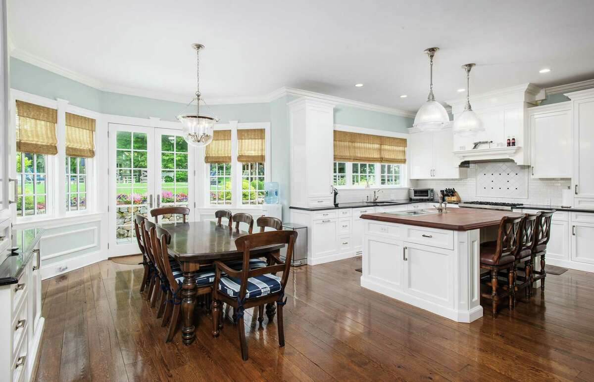 In the sizable gourmet eat-in kitchen features include a pantry, center island/breakfast bar, ogee-edged granite counters, high-end appliances, and French doors to the backyard.