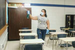 Rosa Castillo sprays disinfectant in the air of a classroom as Pasadena ISD prepares for the start of school.