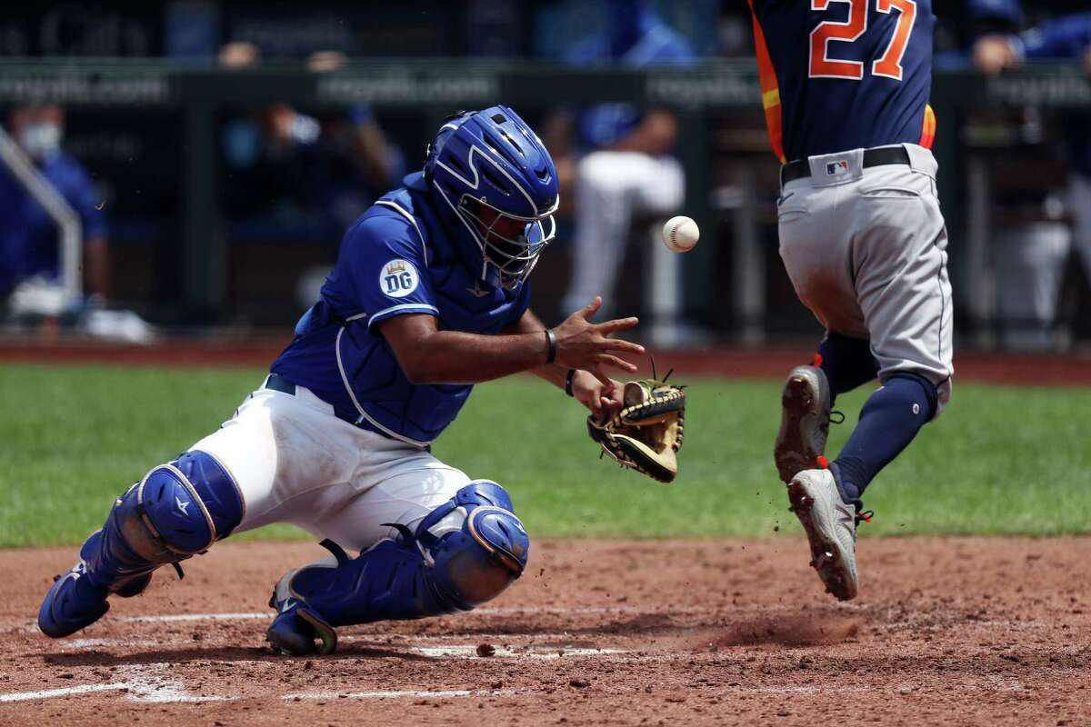 KANSAS CITY, MISSOURI - JULY 21: Catcher Meibrys Viloria #72 of the Kansas City Royals bobbles the ball at home plate as Jose Altuve #27 of the Houston Astros scores during the 4th inning of an exhibition game at Kauffman Stadium on July 21, 2020 in Kansas City, Missouri.