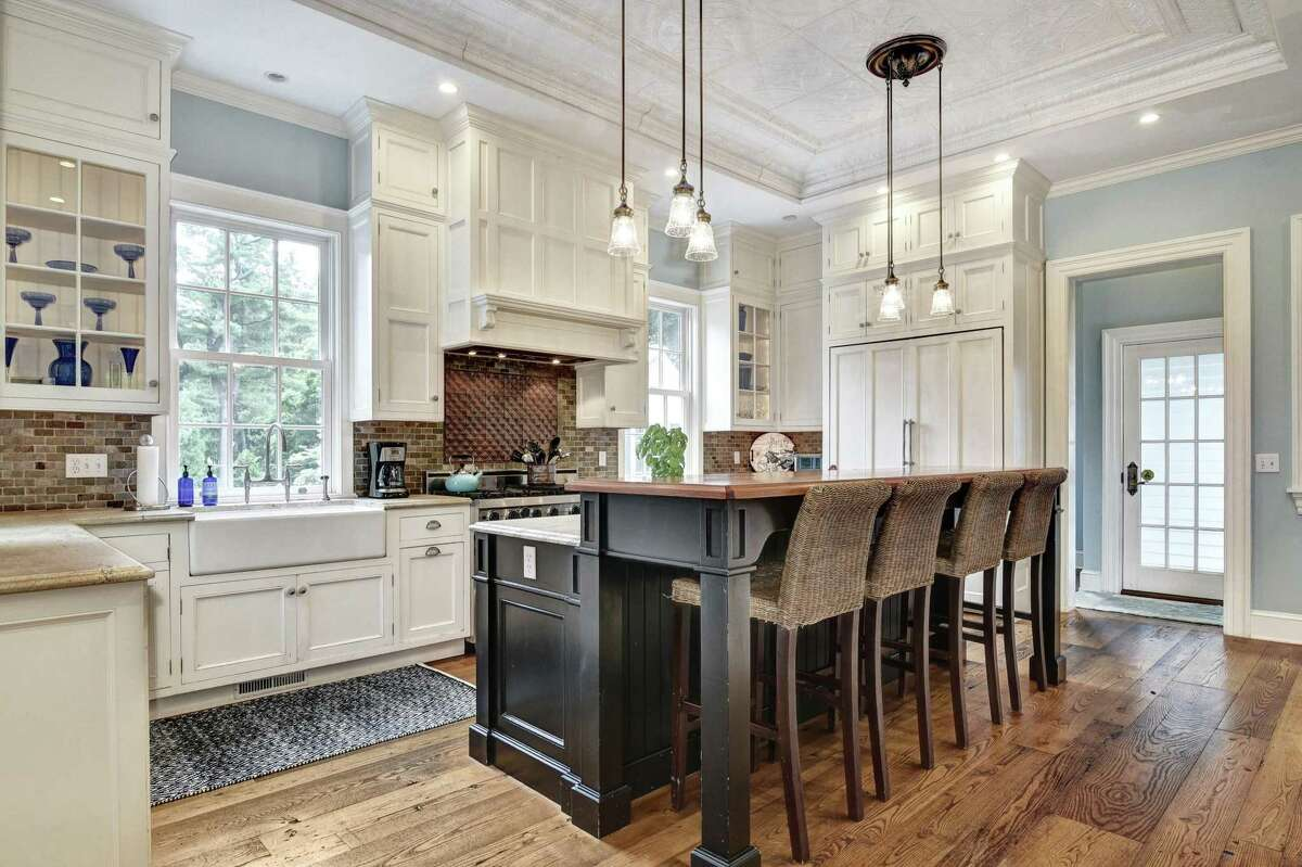 Features in the gourmet kitchen include a two-tiered center island, brushed granite counters, a farm sink, custom cabinetry, 12-foot tall tin ceiling, and Viking six-burner range.