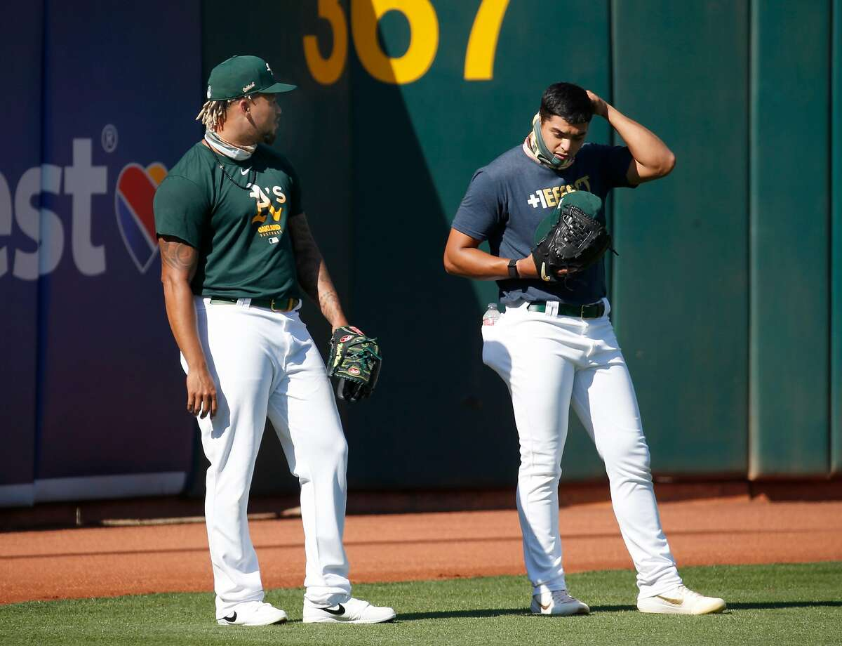 Pitchers Frankie Montas and Jesus Luzardo shag fly balls from batting practice during the Oakland A's summer training camp at the Coliseum in Oakland, Calif. on Saturday, July 18, 2020.