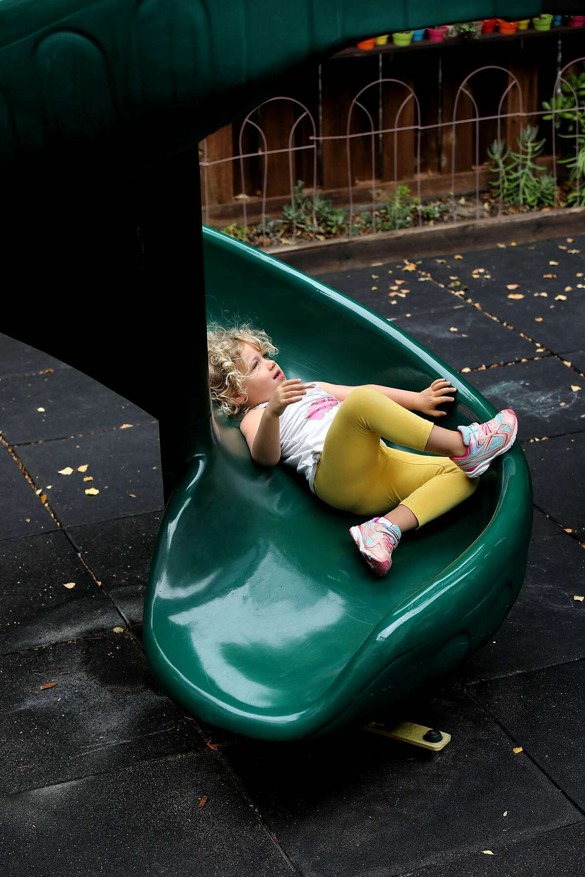 A preschooler comes down a slide at Rockridge Little School on Tuesday, July 21, 2020, in Oakland, Calif. As the pandemic surges and cities and counties stumble through the stop-start process of reopening, the childcare industry -- a vital crutch for many working parents -- appears to be on the verge of collapse. A new report from UC Berkeley serves as a grim I-told-you-so moment for centers and other providers who warned in the spring that long closures, confusing guidelines and heavy restrictions would devastate their already precarious financial models. Parents need childcare to return to work, and many may seek these programs now to fill in for closed public schools. But providers are closing or barely hanging on. Of 953 childcares surveyed for the report, 21% said they had missed a rent or mortgage payment during the pandemic, 81% are operating with fewer children, and 80% have higher cleaning costs.