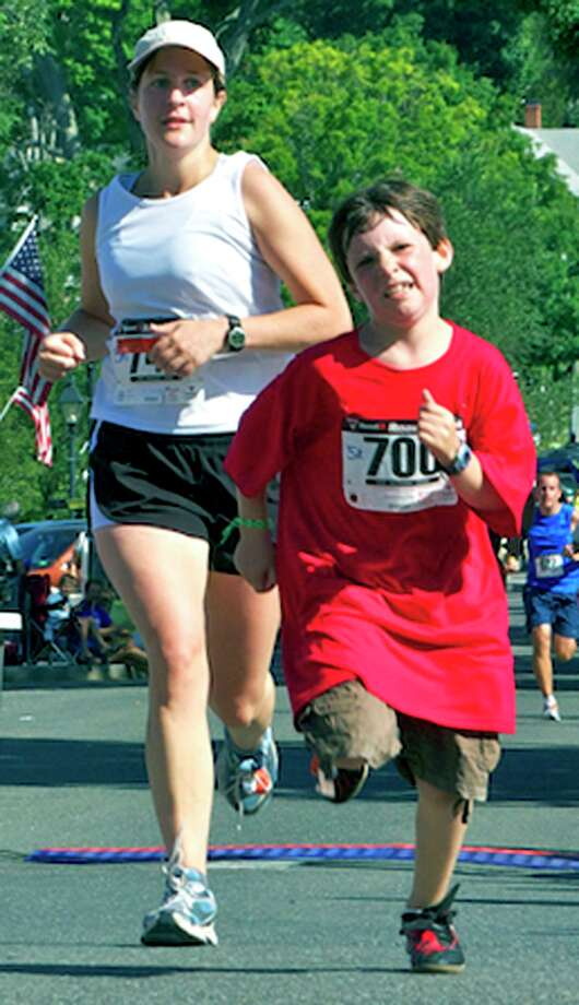 """Due to the coronavirus pandemic, the annual New Milford Village Fair Days was canceled. The popular two-day event would have been held this weekend. The annual 8-Mile Road Race and Village Fair Days 5K is one of the most popular activities of the fair. Above is a picture of 5K runners Amanda Telford of Bridgewater and Ryan Fanella, then 9, of New Milford during the 2010 8-Mile Road Race and 5K. If you have a """"Flashback"""" photograph you'd like to share, contact Deborah Rose at drose@newstimes.com. Photo: File Photo /Trish Haldin / The News-Times Freelance"""