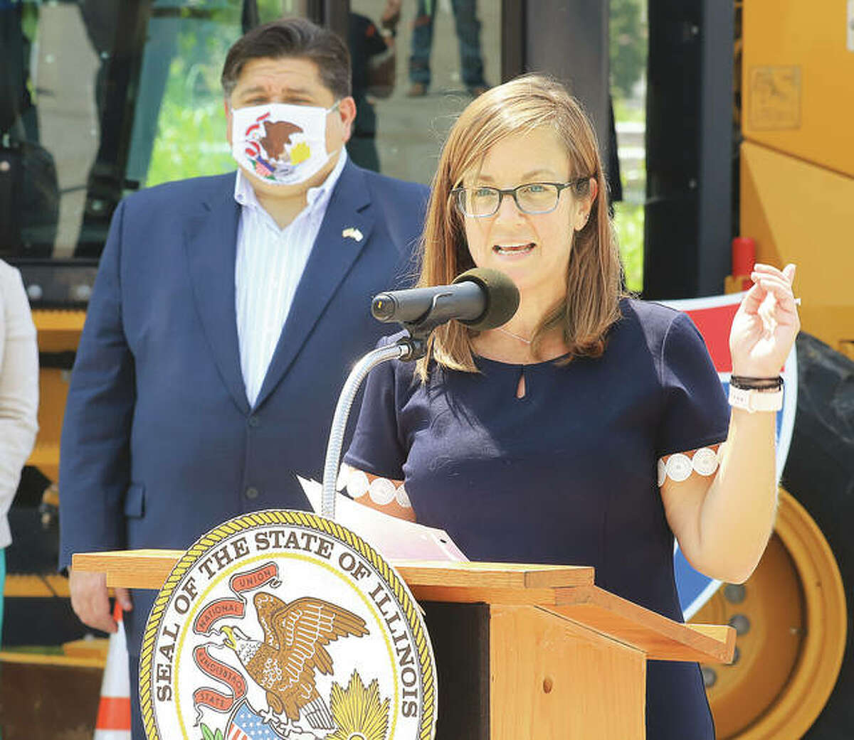 State Rep. Katie Stuart, D-Edwardsville, talks at the Collinsville announcement Tuesday by Gov. J.B. Pritzker, background, of the state's new $21.3 billion multi-year road and bridge improvement plan.