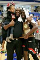 Wagner coach Rodney Clark, center, celebrates the Thunderbird's Regional championship with Braelon Seals, right, and his two-year-old daughter, Rilynn, at the conclusion of their Class 5A Regional final game with Harlan at Northside Gym on Saturday, March 7, 2020. Wagner advanced to the state tournament with a 64-48 victory over Harlan.