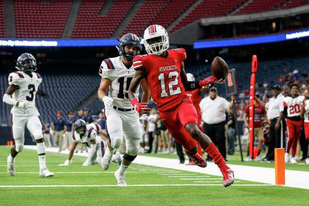 Atascocita Eagles Keith Wheeler (12) scores a touchdown defended by Tompkins Falcons middle linebacker Michael Spath (15) during the first half of the high school football playoff game between the Tompkins Falcons and the Atascocita Eagles at NRG Stadium in Houston, TX on Saturday, November 30, 2019. The Eagles lead the Falcons 35-3 at halftime.