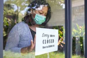 Portrait shot of an Asian restaurant owner putting a closing down poster into a door window due to Covid 19 outbreak