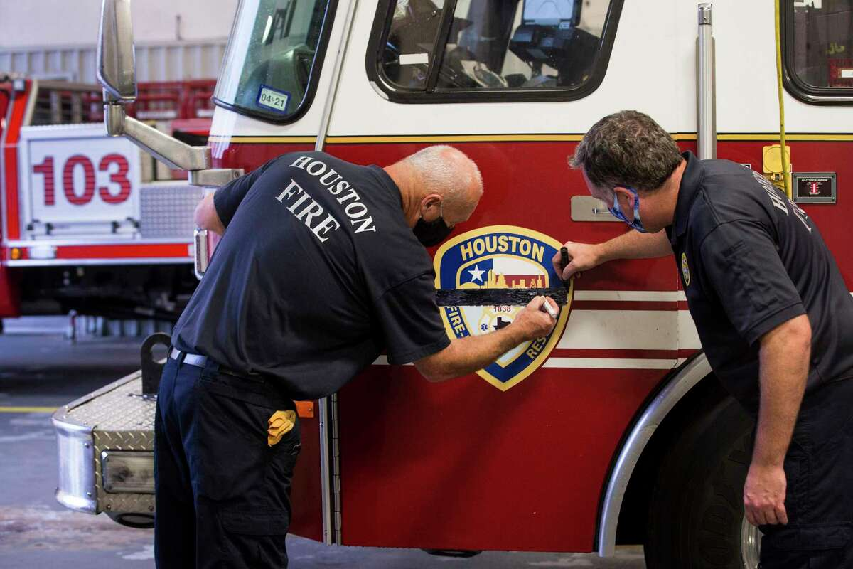 Firefighers Jerry White, left, and Mark Cusic color in a memorial strip of tape, placed across the HFD logo, to honor fallen fire Capt. Leroy Lucio at Station 103 on Tuesday, July 21, 2020 in Kingwood. Lucio, a 29-year veteran of the department, died Monday from COVID-19, according to Chief Sam Peña. He was battling the virus at a hospital in his hometown of San Antonio and is the first firefighter in Houston to die from the virus, the Houston Professional Fire Fighters Association said.