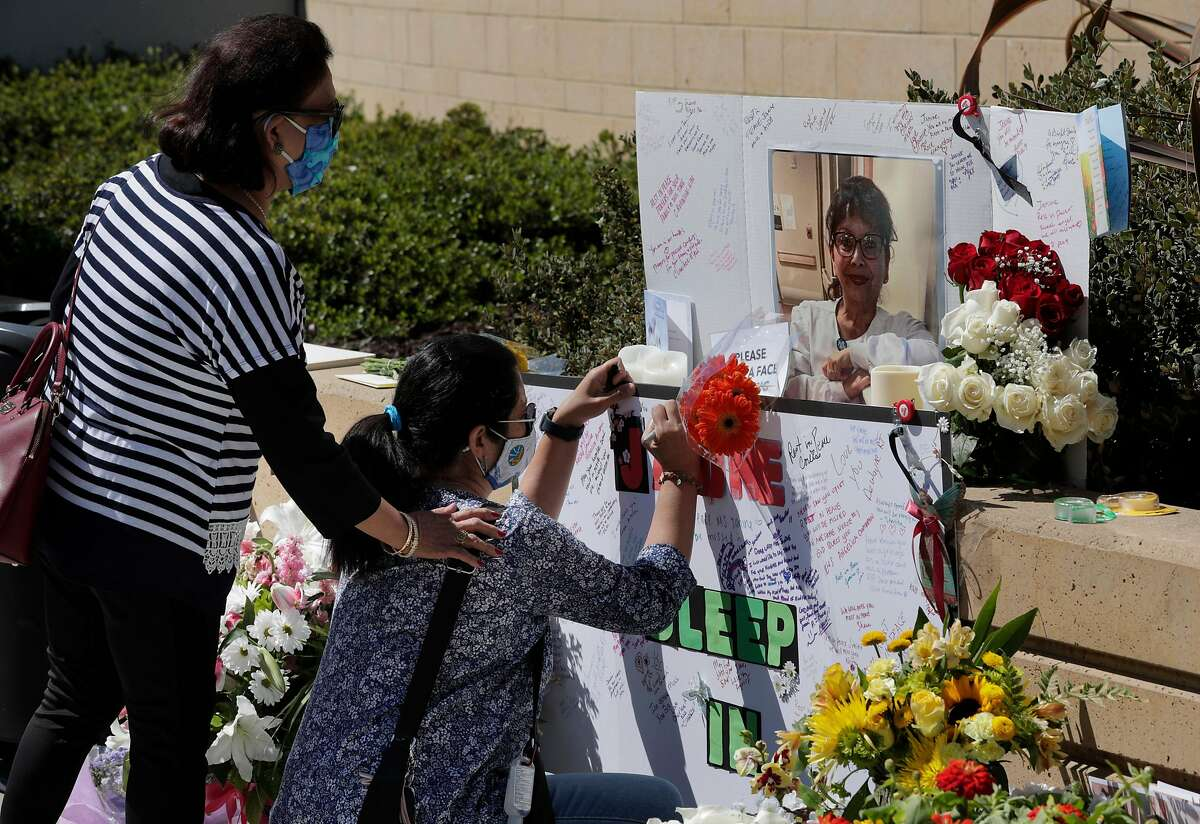 Nurse Jennie S-M (did not give full last name) signs a memorial as colleague Vessie Tacla supports her during a vigil for nurse Janine Paiste-Ponder, who died of COVID-19 after working with patients with the disease at Alta Bates Summit Medical Center in Oakland , Calif., on Tuesday, July 21, 2020. Colleagues will remembered the nurse of more than 25 years at a vigil Tuesday. They said she didn't sign up to sacrifice her life, and called upon the hospital to provide more protective equipment and testing after exposure to patients. Across California, 19,734 health care workers have tested positive and 107 have died.