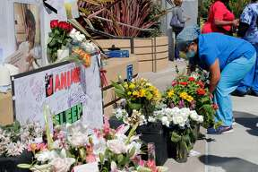 Myra Juarez leaves a bouquet of flowers at a memorial during a vigil for nurse Janine Paiste-Ponder, who died of COVID-19 after working with patients with the disease at Alta Bates Summit Medical Center in Oakland , Calif., on Tuesday, July 21, 2020. Colleagues will remembered the nurse of more than 25 years at a vigil Tuesday. They said she didn't sign up to sacrifice her life, and called upon the hospital to provide more protective equipment and testing after exposure to patients. Across California, 19,734 health care workers have tested positive and 107 have died.